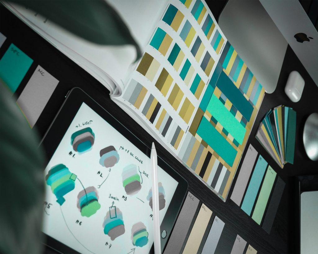 Työpöytä mikä on täynnä graafisen suunnittelun työkaluja joka kuvastaa hemo solutions kotisivujen graafista suunnittelua Uudenmaan alueella.